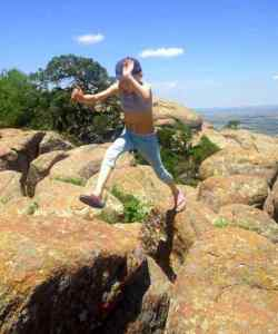 Image of girl in cap jumping over rock crevice on mountain top