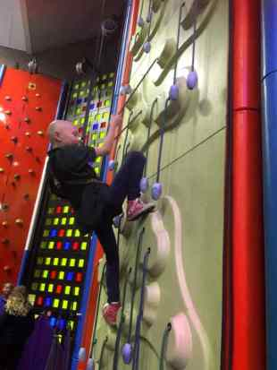 Image of girl with no hair in cub uniform on indoor climbing wall