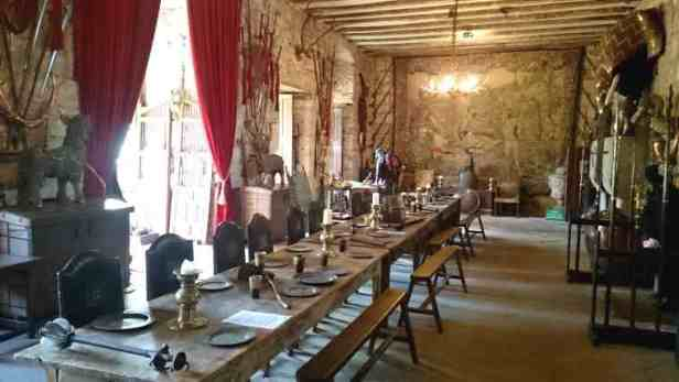 Image of huge refectory table in great hall laid with medieval condiments and weaponry