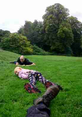 Image of man, child and woman's booted foot lying on grass at bottom of slope with trees in background