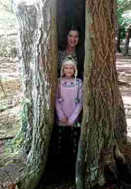 Image of woman and child standing in crack of huge hollow tree trunk