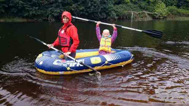 Image of woman and girl waving paddle above her head wearing buoyancy aids in blue and yellow inflatable dinghy on river