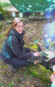 Image of woman cooking on trivet on camp fire in woods