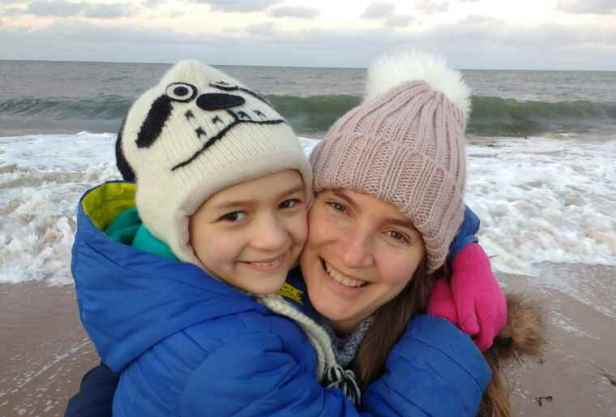 Image of smiling mother and child in wolly hats hugging on beach with crashing waves behind