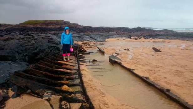 Image of woman standing among iron skeleton of shipwreck on sandy beach