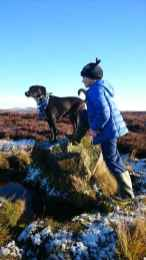 Image of black dog sitting on boulder in snowy moorland next to girl in blue jacket and black hat with one foot on same boulder