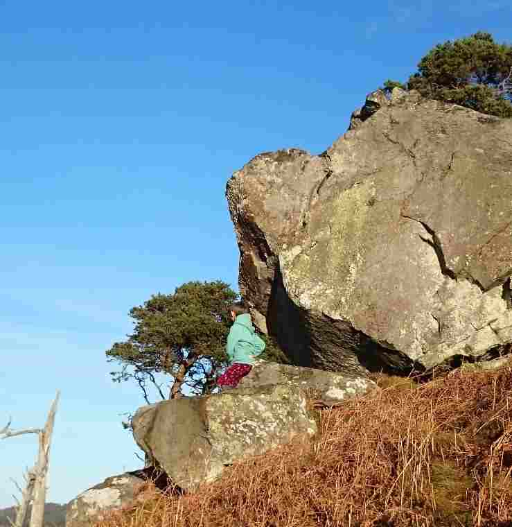 Image of child sitting on large bouler on side of hill with huge overhanging rock above and trees and blue sky in background