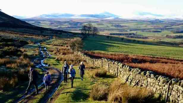 Image of group of 4 adults and child hiking up a muddy track with green fields and snow capped hills in distance