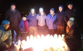 Image of group of people in the dark stood behind a bright fire lit in the snow