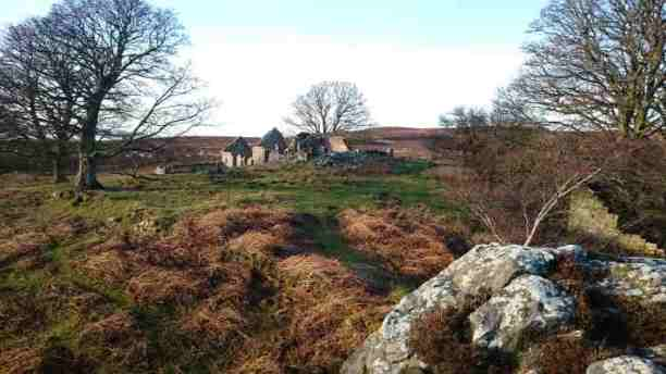 Image of ruined building viewed from rocky crag in foreground with bare trees around and moor in background