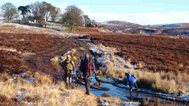 Image of two men walking along muddy track with girl jumping in ice puddles on moor with wide vista and ruined house in background