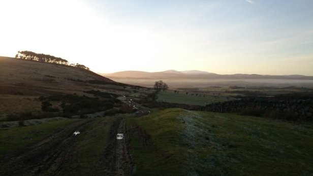 Image of wide landscape at sun down with puddles in the winding track down a hill with higher hill and silhouetted trees to left and misty lowland in distance
