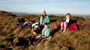 Image of woman and two girls in winter gear sitting in heather having a picnic with distant hills in background