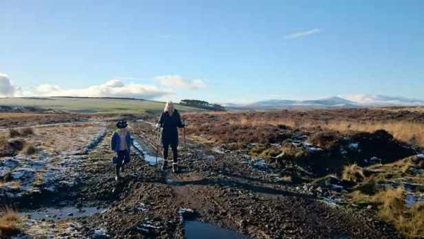 Image of woman with walking poles and child in blue coat walking on muddy track with huge moorland landscape behind