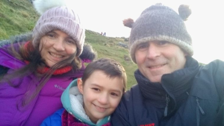 Selfie image of woman, girl and man in winter coats and hats at bottom of steep slope