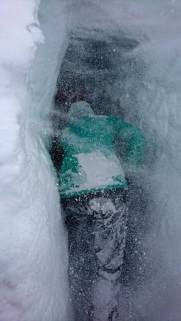 Image of person's back in green snow jacket and dark trousers leaning into snow hole entrance with snow piling up on clothing