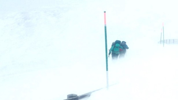 Image of 2 people battling through wind, snow and spindrift on snowy hill with snow-covered fence in background and depth pole at front