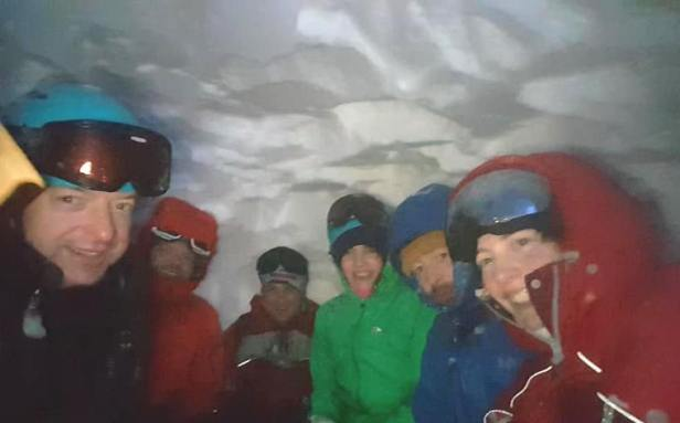 Image of 6 adults in snow gear sitting in snow hole