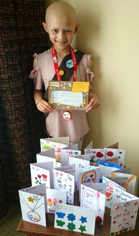 Image of bald headed child cancer patient behind table of get well cards wearing Brownie sash and carrying Brownie investment certificate