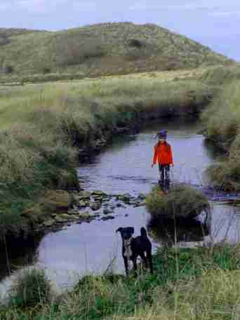 Image of child standing on mini island in coastal stream with dunes around