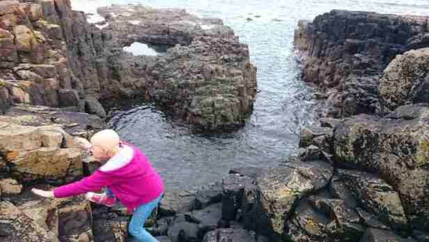 Image of girl in magenta jacket and blue leggings with no hair scrambling on coastal rocks with sea behind