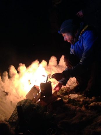 Image of man in blue jacket with head torch working on camp fire in snow at night