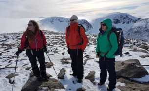 Image of three people in coloured snow gear standing on snow and rock covered ground with mountain ridge in background appearing out of cloud