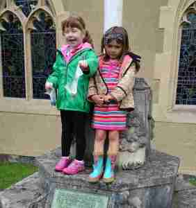 Image of two children in colourful outdoor clothing standing on stone monument steps