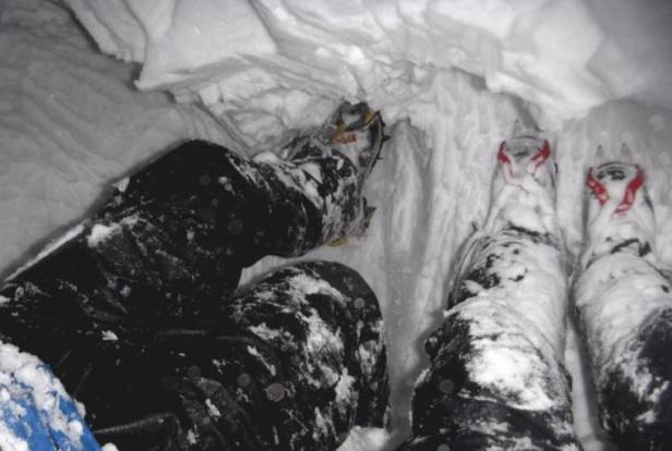 Image of two pairs of legs in waterproof snow gear and crampons scouring snow from roof of snow hole