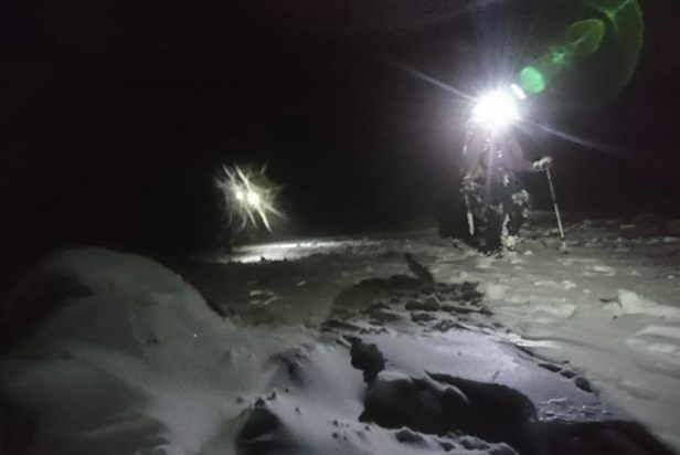 Image of two people with head torches walking on snowy ground in the dark