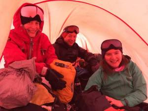 Image of two women and a man in snow gear inside an orange group shelter