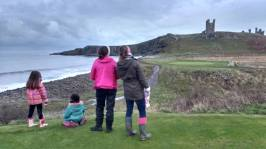 Image of two women and two children looking at distant castle ruins on top of steep rocky sill with crashing waves to left
