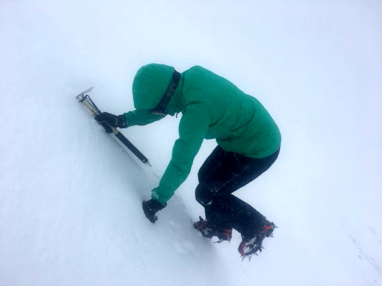 Image of woman in green ski jacket and dark trousers with crampons, ski goggles and ice axe climbing steep snow slope