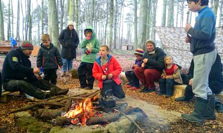 Image of adults and children around a camp fire in the woods with tarp in background