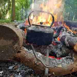 Image of black metal kettle on metal trivet heating over flaming campfire in woods