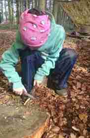 Image of child in outdoor gear sitting on log in woods whittling with a knife