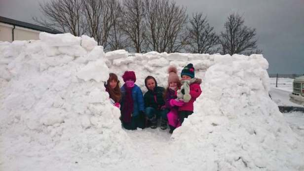 Image of five children in outdoor gear sat inside snow igloo without roof on in deep snow with house and trees behind