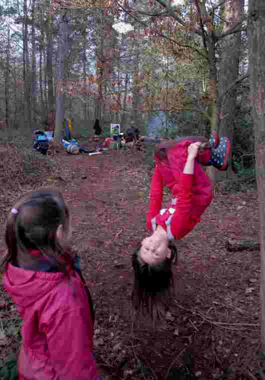 Image of girl in red hanging upside down from a tree branch in woods with second girl watching and camp fire behind
