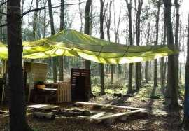 Image of parachute shelter set up in woodland over camp fire with wooden boards in background