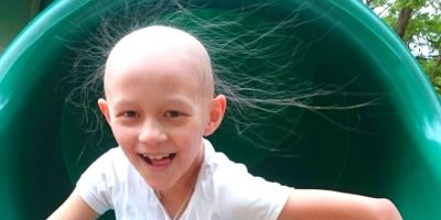 Image of smiling child in white T-shirt with almost bald head and strands of hair standing out in static at the bottom of a plastic green slide
