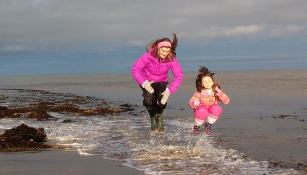 Image of woman and child in waterproof gear jumping in the air about to splash land in waves at the seashore with seaweed on beach and sky behind