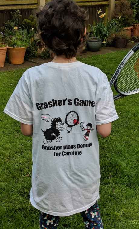 Image of girl showing back of white T-shirt with words 'Gnashers Games' Gnasher plays Dennis for Caroline' holding tennis racquet