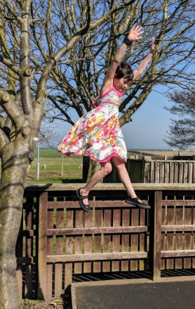 Image of girl in sundress and black pumps jumping from tree onto tarmac with sea in background