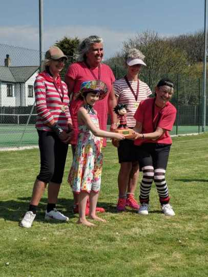 Image of girl in sundress and hat handing tennis trophy to 4 women in red and black kit, on grass