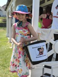 Image of girl in sundress and hat holidng charity collection bucket outside white building