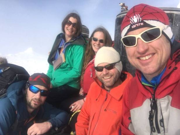 Image of group of 5 people in outdoor gear with snow-covered cairn in background