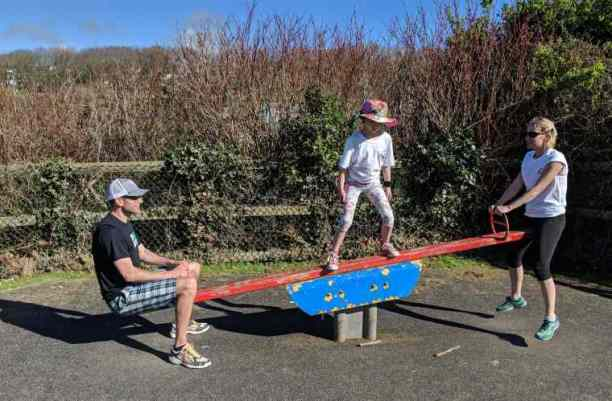 Image of man, woman and child on red and blue seesaw with hedge behind