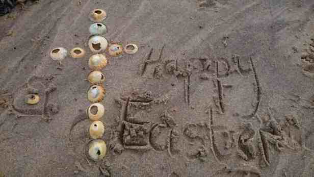 Image of cross made of shells in sand with the words happy easter written in sand
