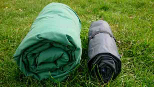 Image of two rolled up blankets on grass, one large green the other smaller and dark grey