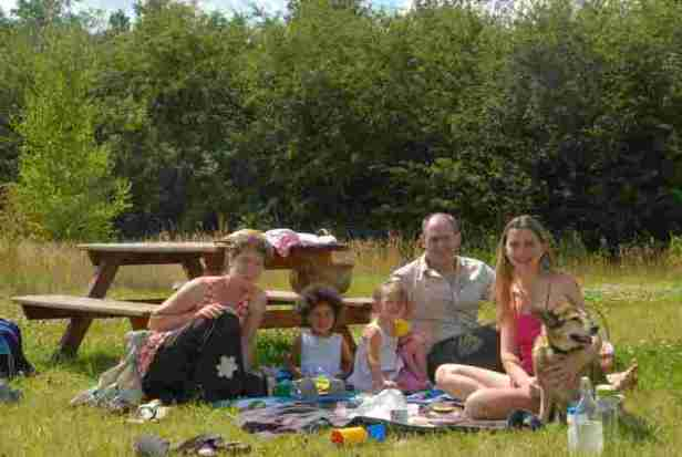 Image of two women, a man, two girls and a dog eating on picnic blanket on grass with picnic table and trees behind